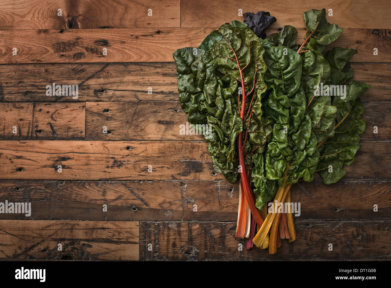 group of red and orange chard leaves with bright coloured stems Organic vegetables freshly picked and placed on Stock Photo