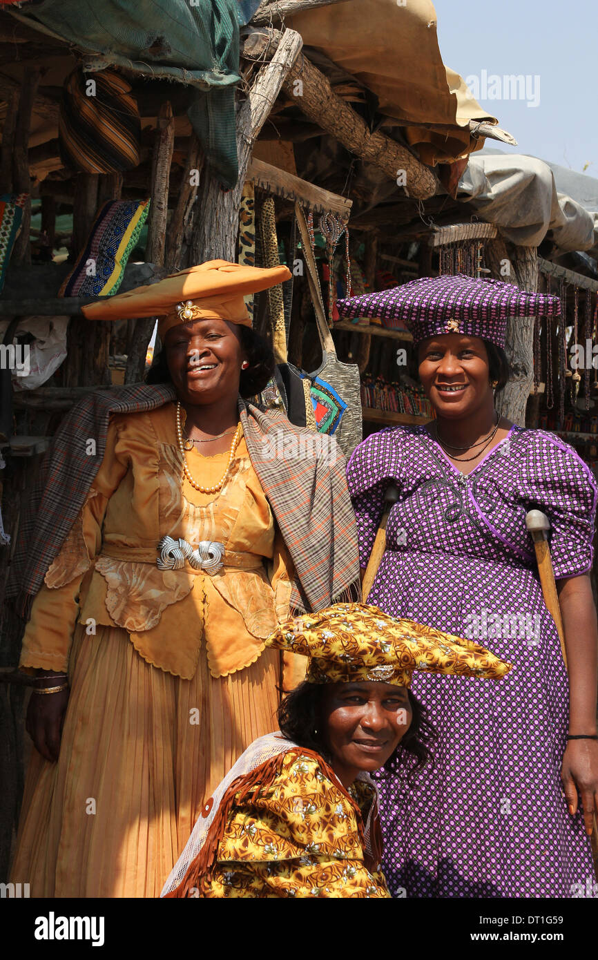 Three Herero tribe women in Namibia,wearing their traditional German era inspired Victorian dress and  cow-horn Stock Photo