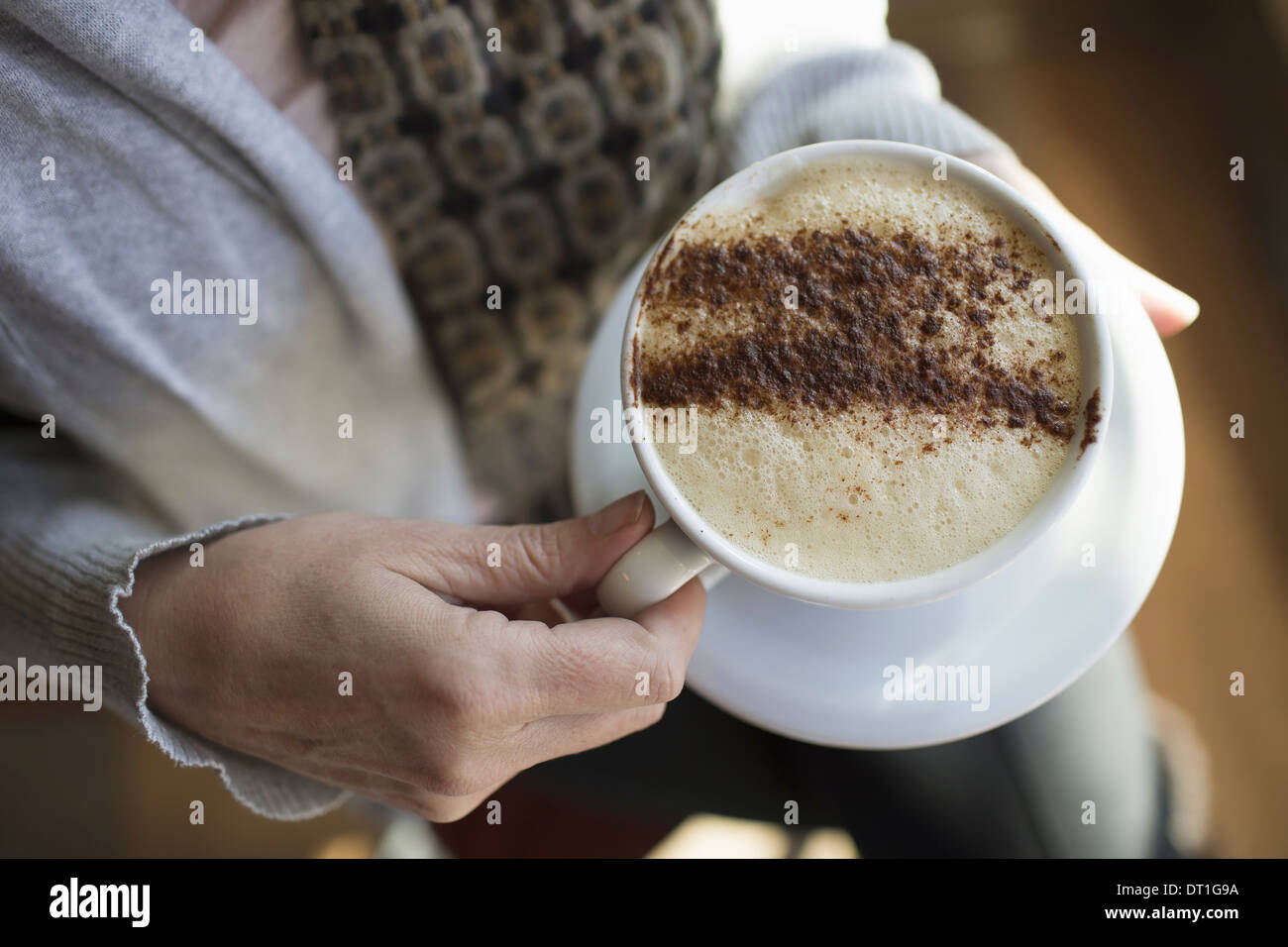 A person holding a full cup of frothy cappuccino coffee in a white china cup Chocolate powder sprinkled in a pattern - Stock Image