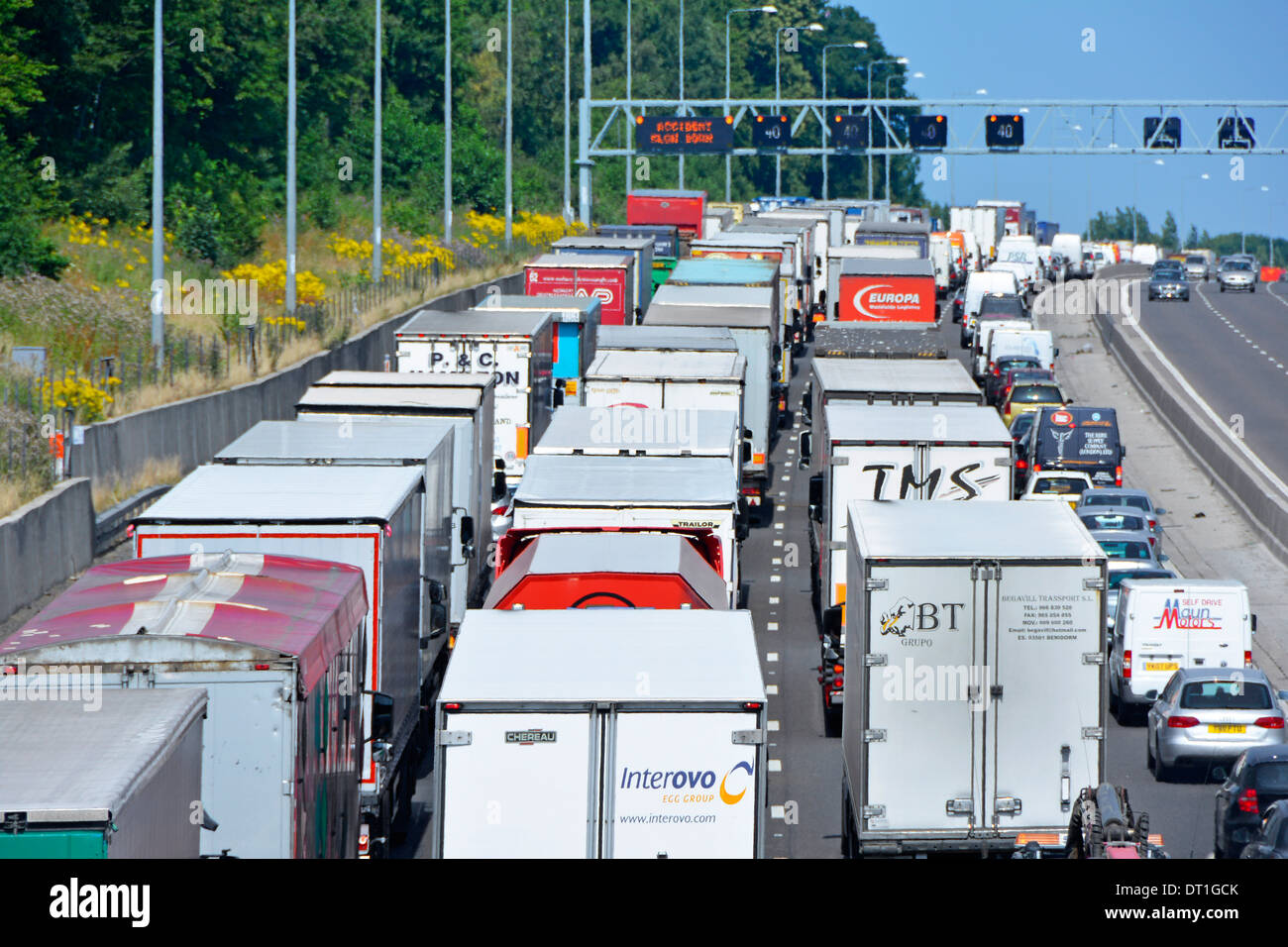 Four lane M25 motorway and gridlocked (mainly) trucks with articulated trailers stuck in queue because of an accident - Stock Image