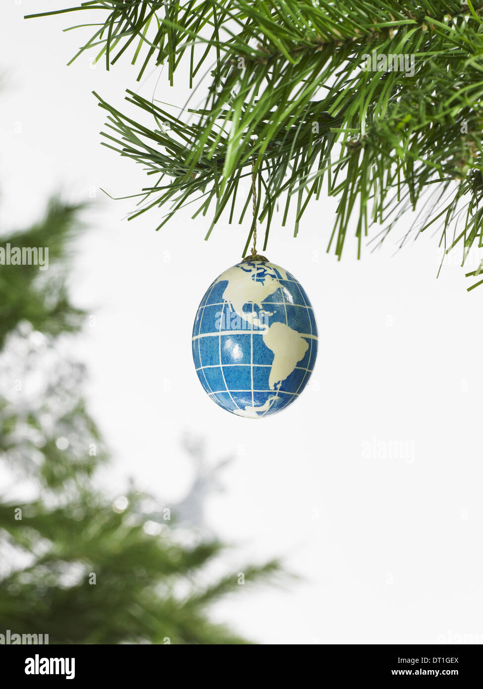 decorations A pine tree branch and a blue and white bauble A globe with continents outlined on a blue background - Stock Image