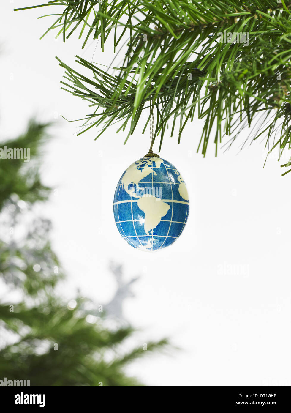 Green leaf foliage and decorations A pine tree branch and a blue and white bauble A globe with continents outlined - Stock Image