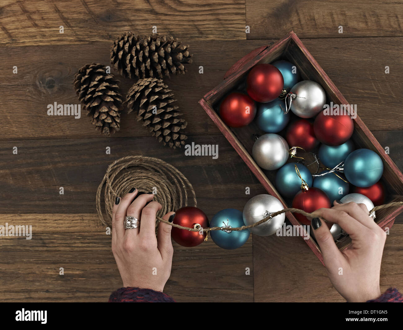 A woman threading Christmas shiny round ornaments on a piece of string A small group of pine cones - Stock Image