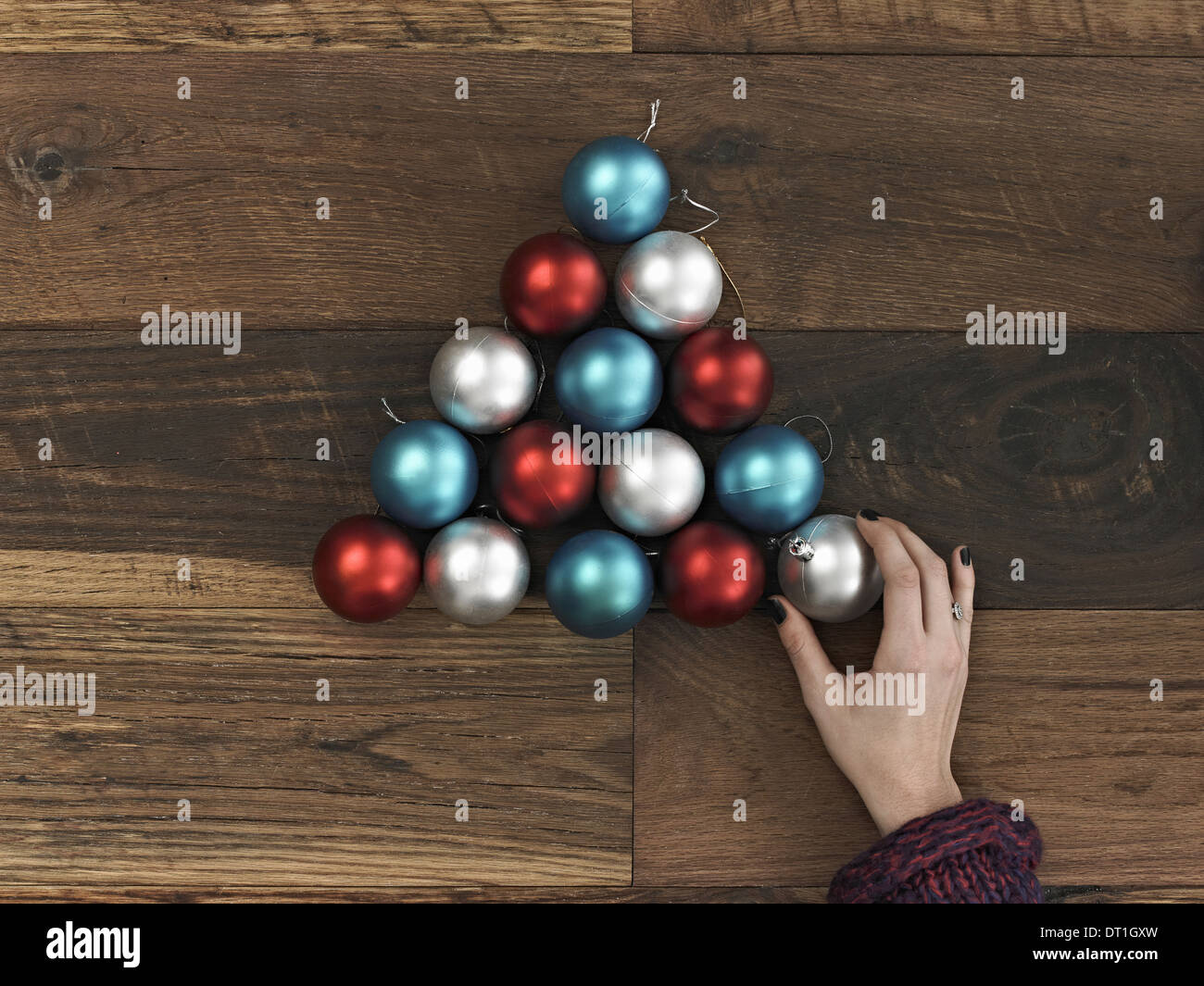A collection of blue red and silver ornaments A Christmas tree shape A person's hand placing the final ball - Stock Image