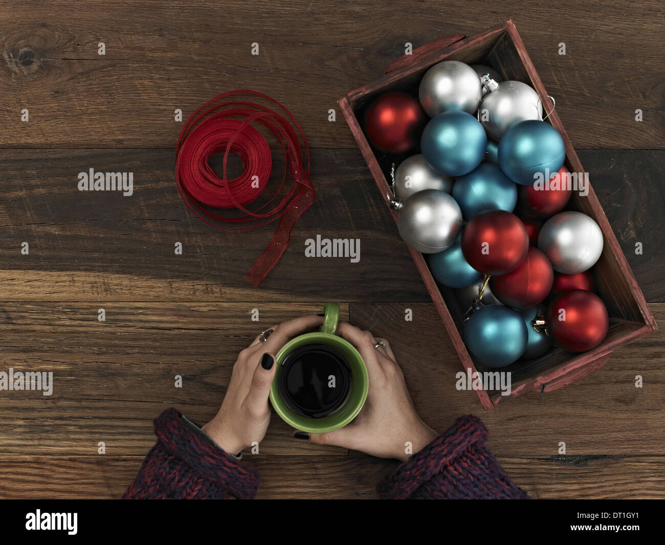 blue red and silver ornaments and red ribbon in a box on a wooden board A hand curled around a cup of coffee Taking a break - Stock Image