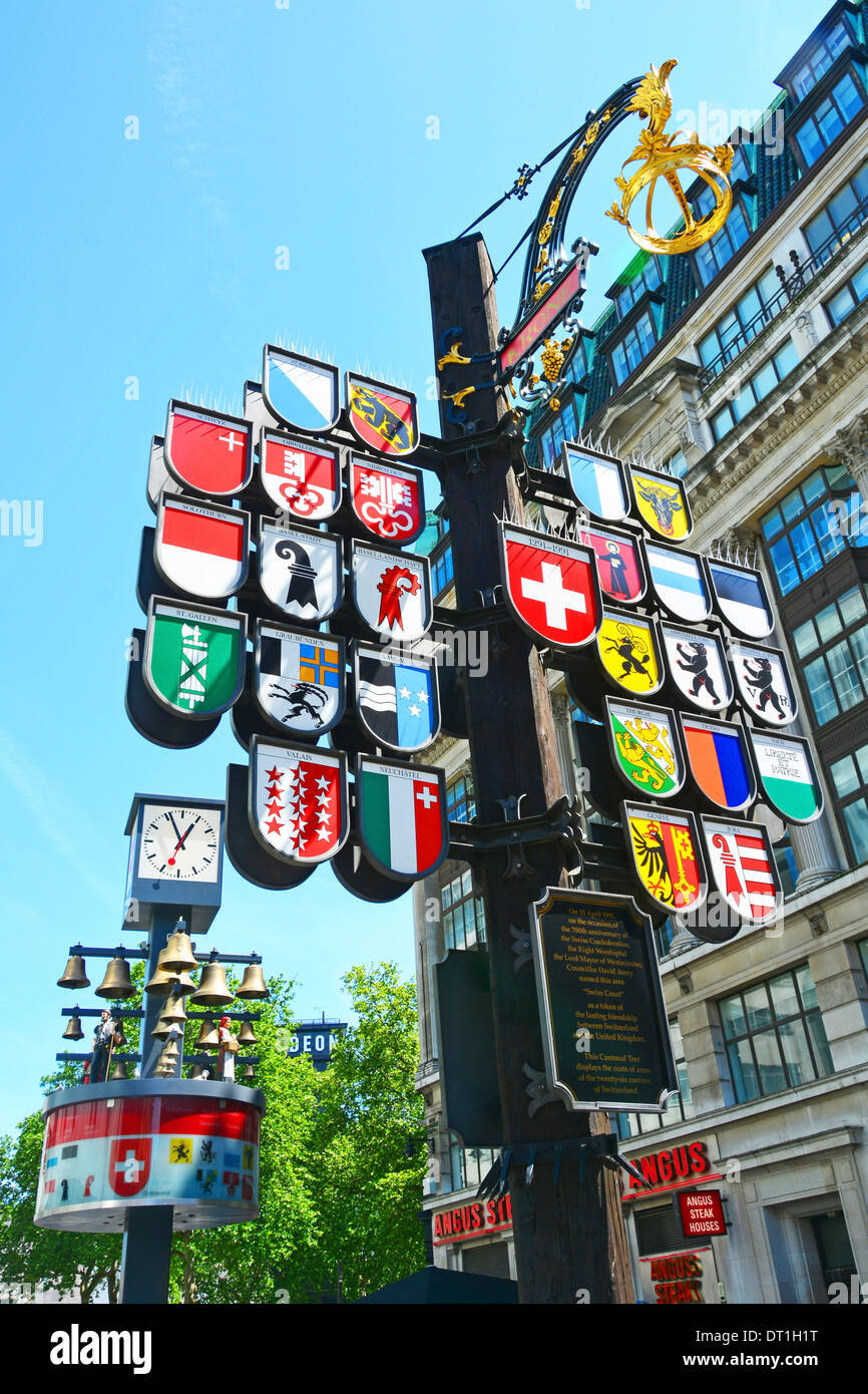 Cantonal tree display of the twenty six Cantons of Switzerland in Leicester Square with bells from the old Swiss Centre beyond - Stock Image