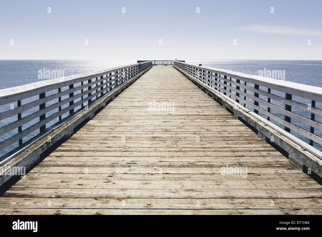 A long pier with railings extending out over the Pacific Ocean leading to the horizon - Stock Image