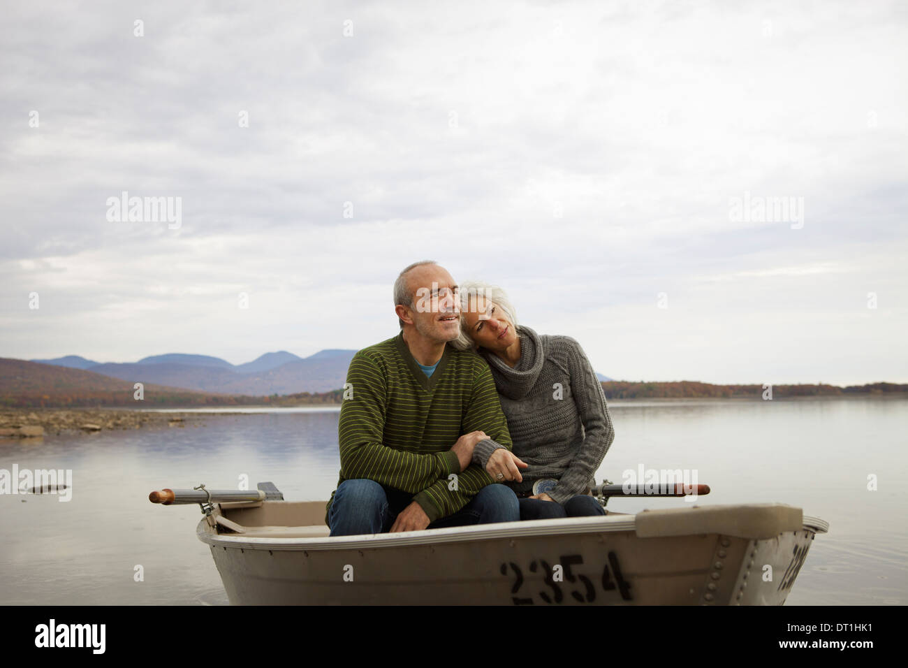 A couple man and woman sitting in a rowing boat on the water on an autumn day - Stock Image