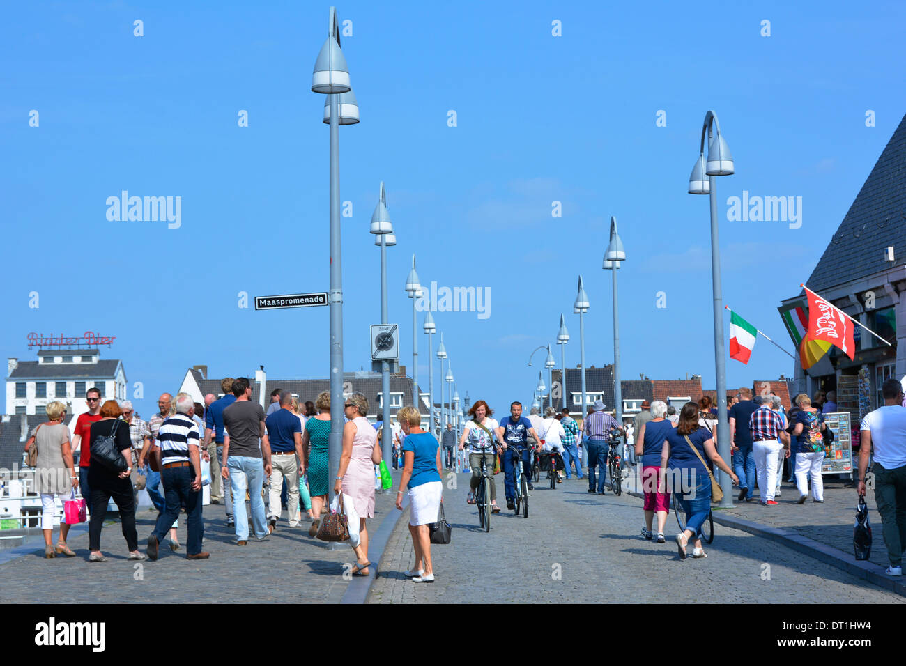 Street scene pedestrians and cyclists on the Saint Servatius (Sint Servaasbrug) bridge over the river Meuse on a hot summer day - Stock Image