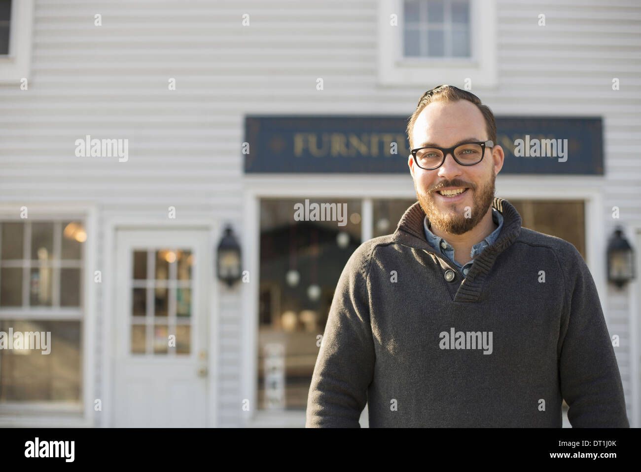 A man standing outside a store on street Antique store - Stock Image