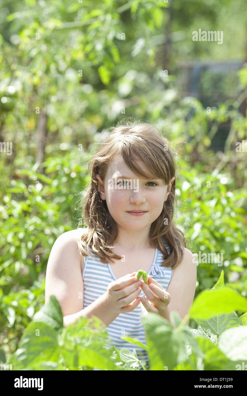 A young girl sitting in among the fresh green foliage of a garden Vegetables and flowers Picking fresh vegetables - Stock Image