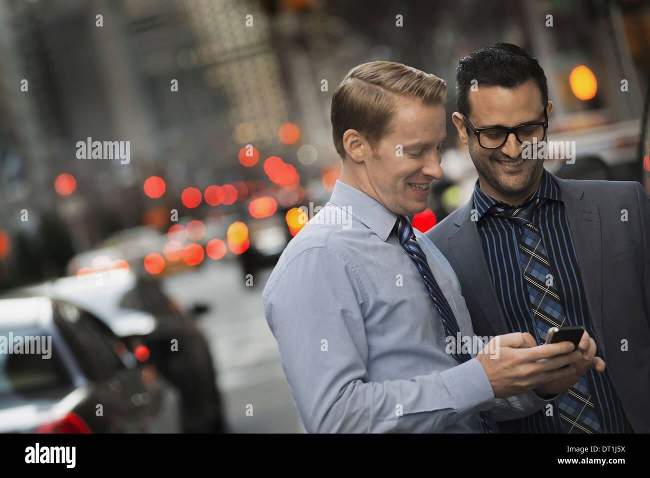 Two men standing together looking at a cell phone display on a busy street at dusk - Stock Image