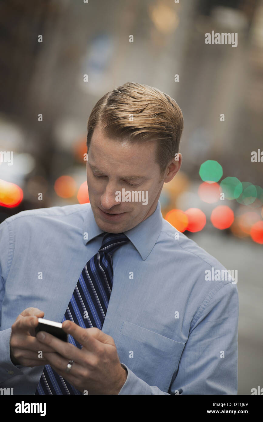 A man in a shirt and tie checking his cell phone standing on a busy street - Stock Image