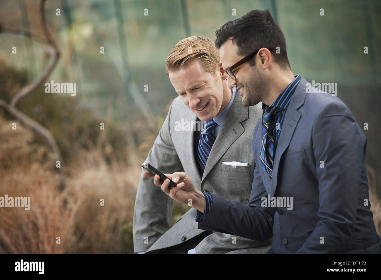 Two men in formal business clothes standing side by side looking at a cell phone screen or mobile phone - Stock Image