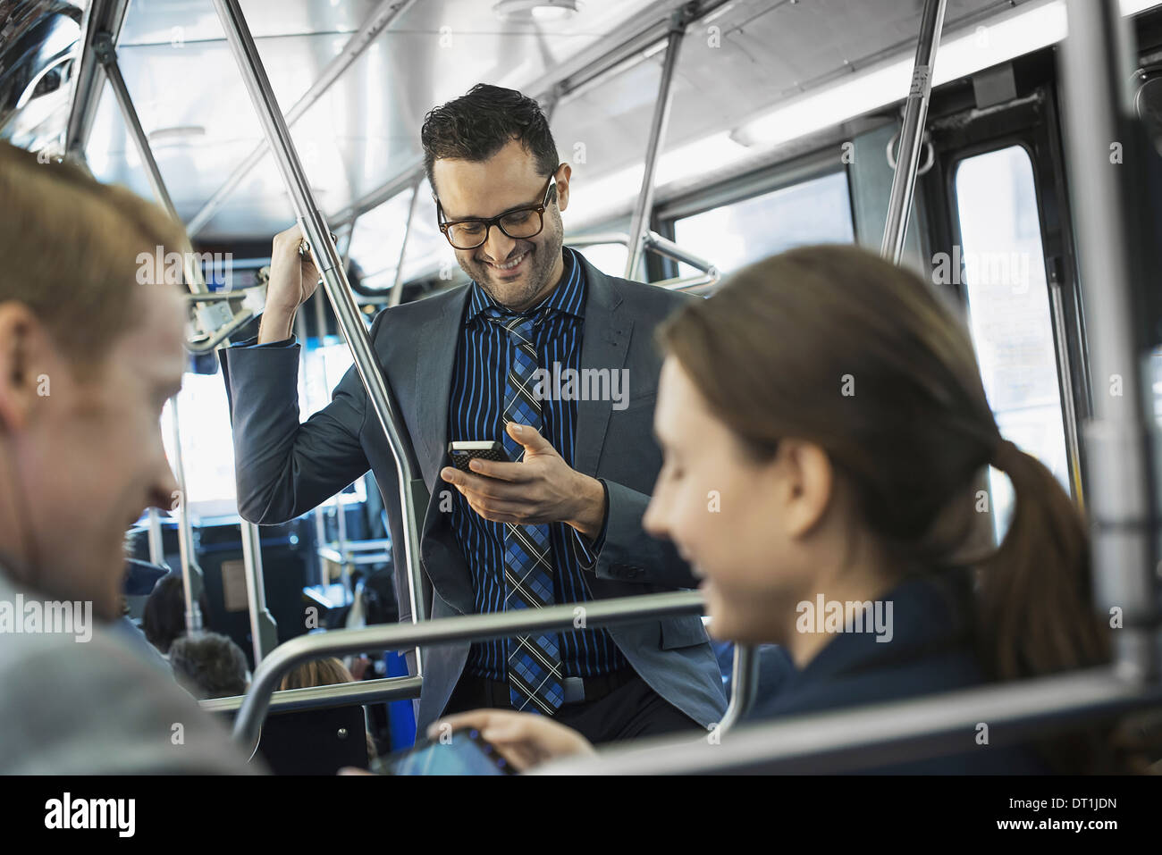 Three people on the move two men and a woman on the bus - Stock Image
