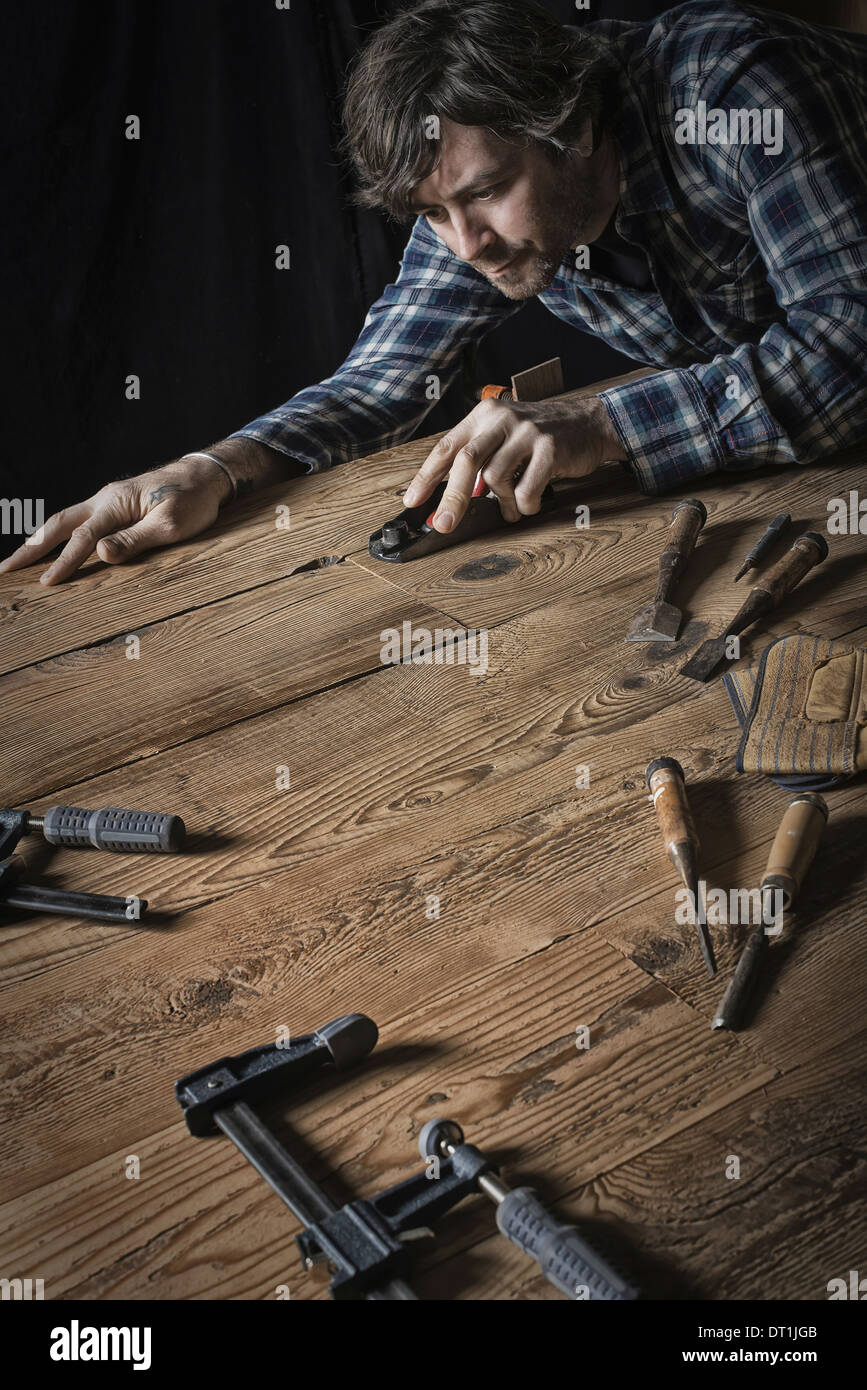 A man working in a reclaimed lumber yard workshop Holding tools and sanding knotted and uneven piece of wood - Stock Image