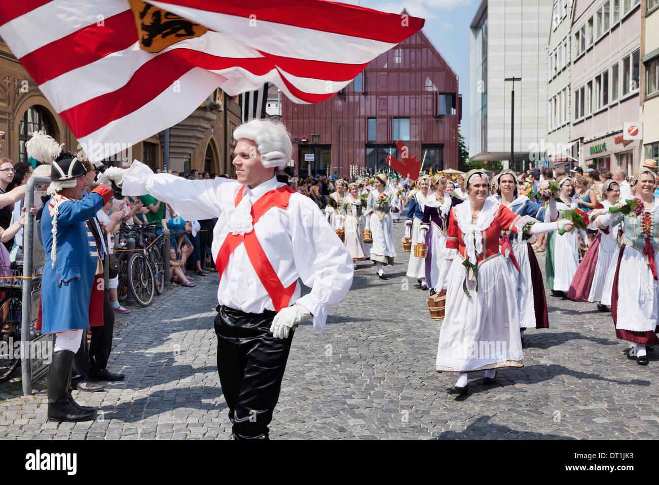 Flag thrower and fisher women in a historical parade at the market place, Fischerstechen, Ulm, Baden Wurttemberg, Germany - Stock Image