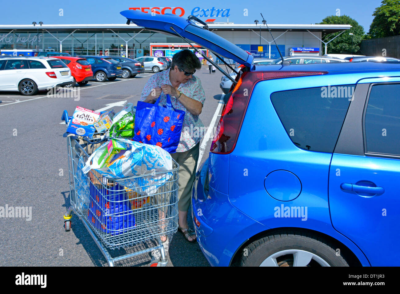 Tesco Extra supermarket store free car park and mature woman loading food shopping into hatchback car - Stock Image