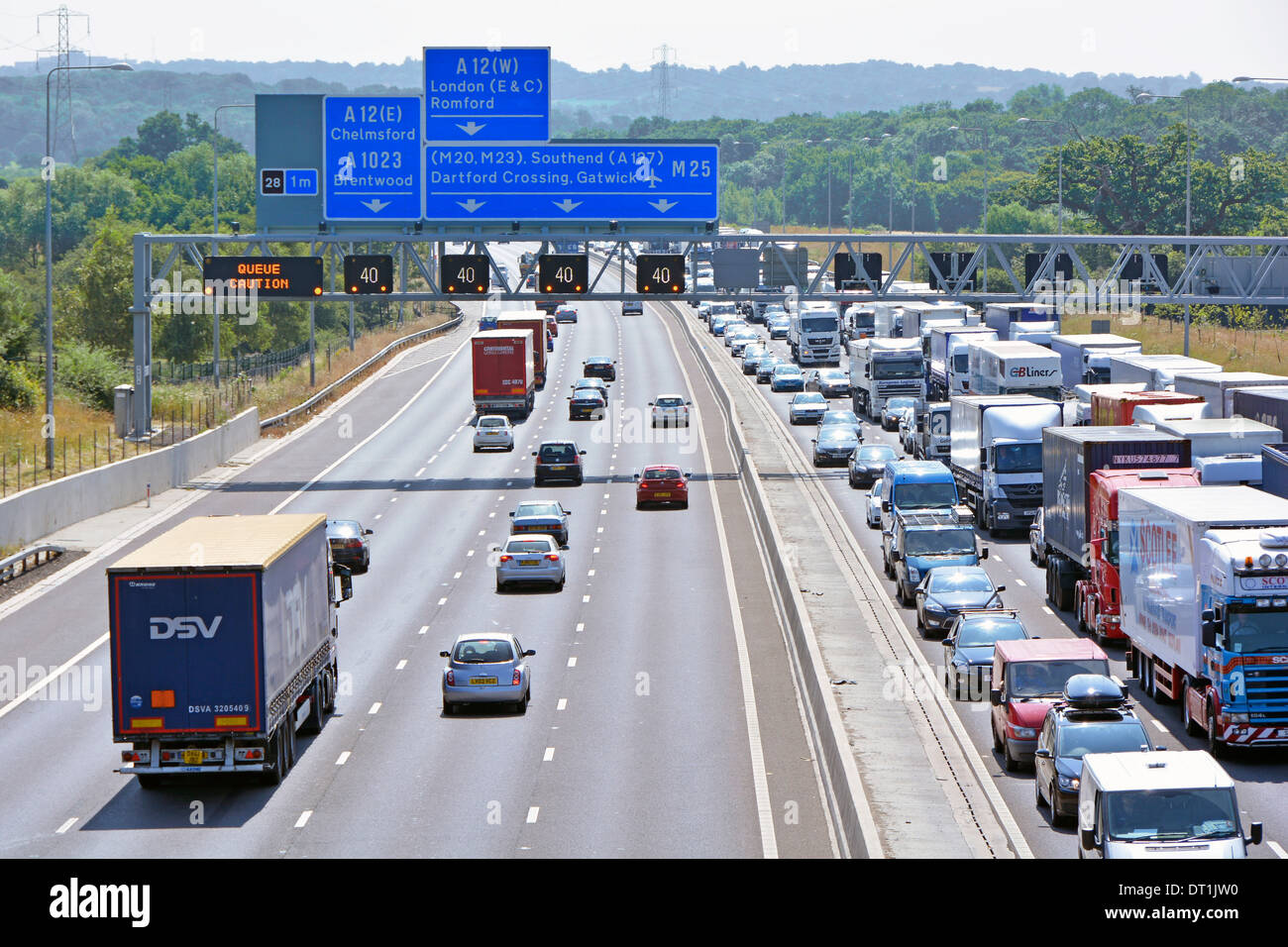 Gantry sign  spanning eight lane M25 motorway at junction 28 with electronic digital display warnings & gridlocked traffic - Stock Image
