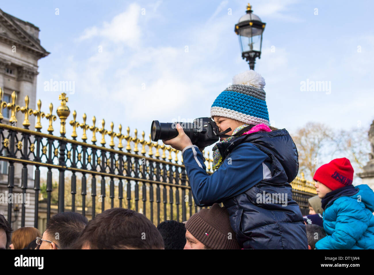 LONDON, UK, 2ND FEB 2014: A young photographer taking pictures of Buckingham Palace on top of a mans shoulders - Stock Image