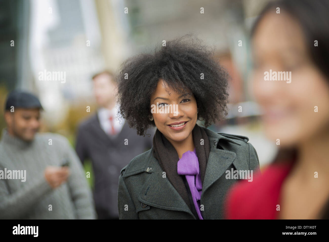 using mobile phones and talking to each other Men and women - Stock Image