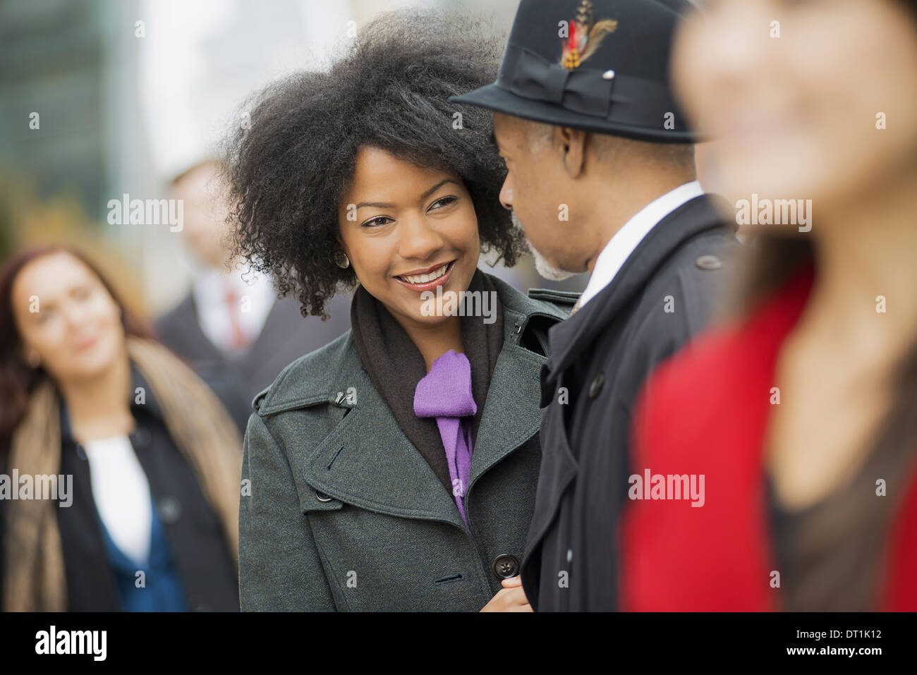 A group of people on the go on the street A man and woman standing close together - Stock Image