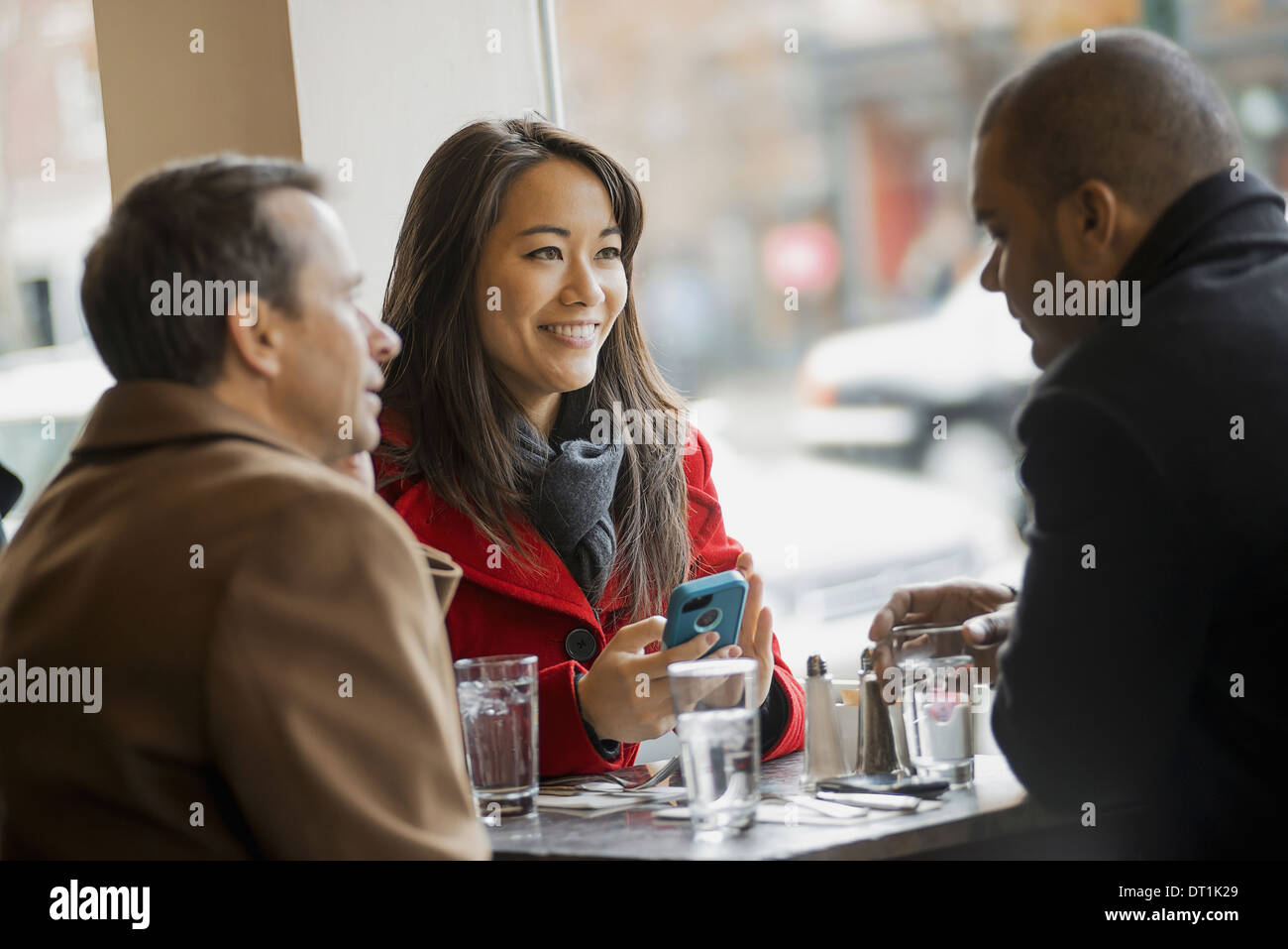 A group of people on the go using mobile phones and talking to each other In a coffee shop - Stock Image