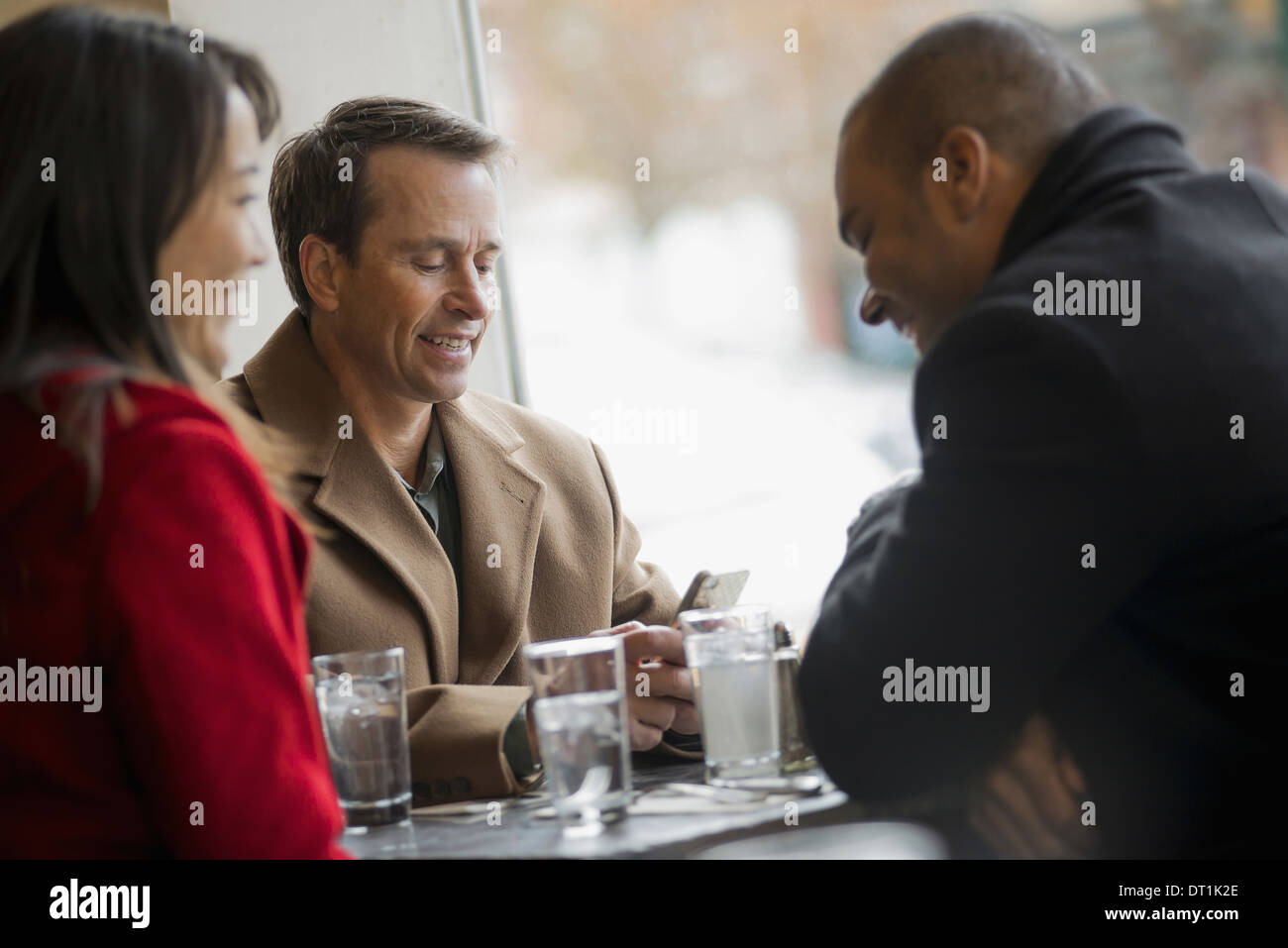 A group of people on the go using mobile phones and talking to each other In a coffee shop Stock Photo