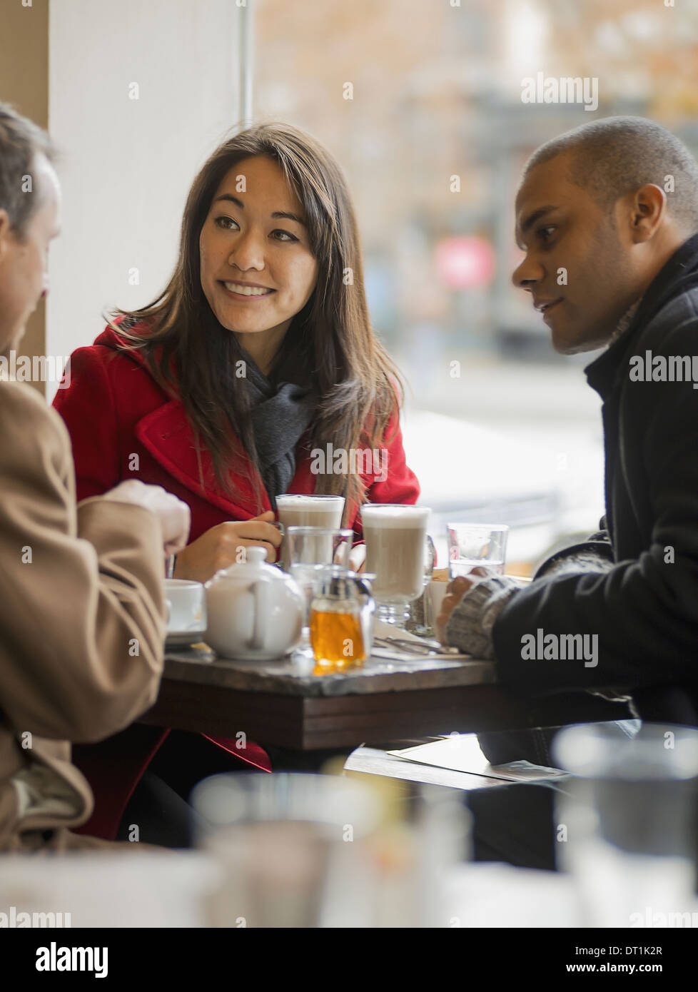 A group of people on the go Three people in a coffee shop sitting at a table and talking to each other Stock Photo