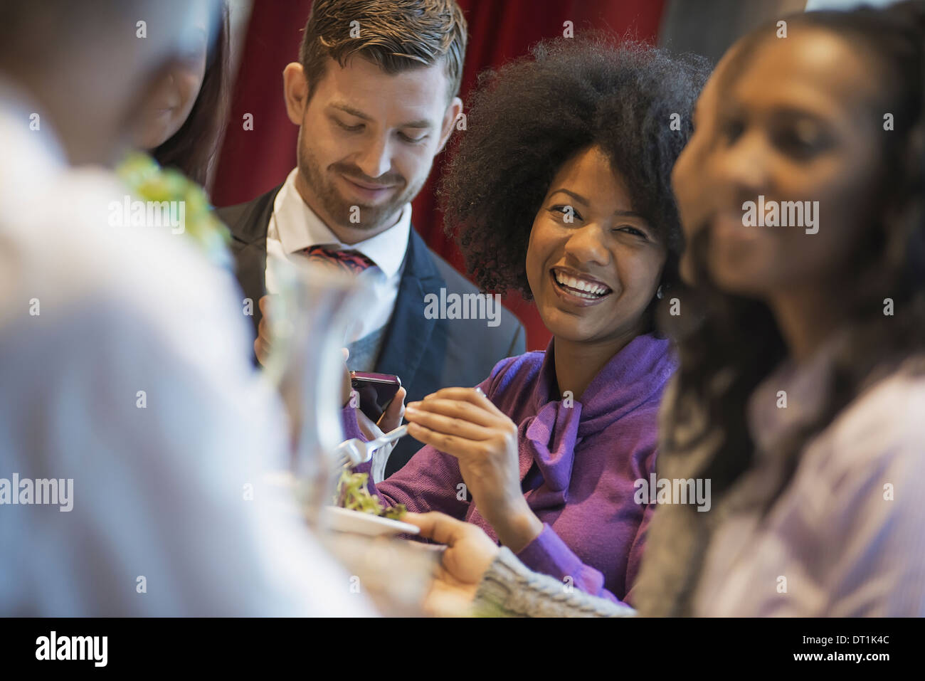 A group of people in a coffee shop one using a mobile phone and others talking to each other Men and women - Stock Image