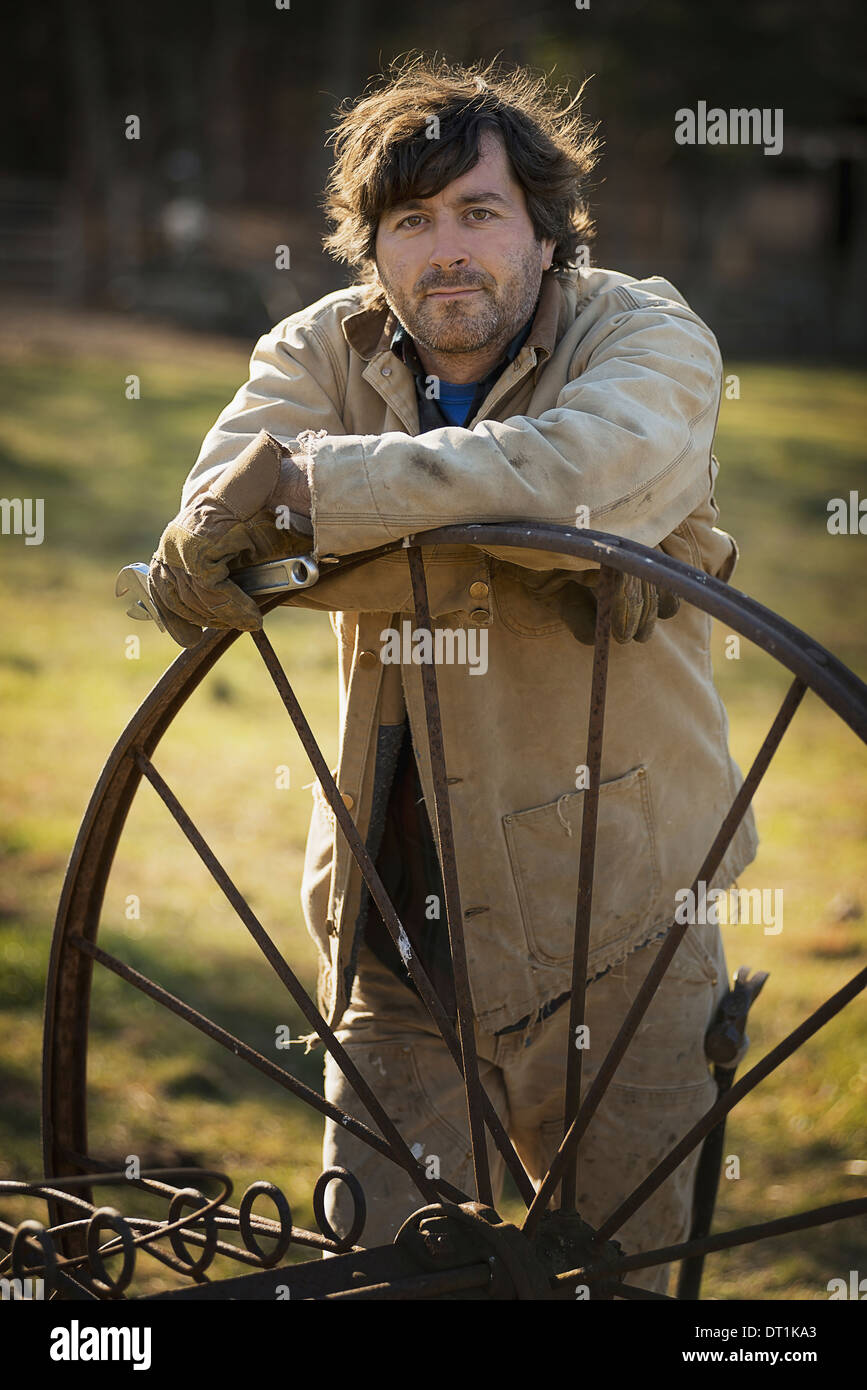 Working on an organic farm A man in overalls wearing work gloves leaning on a round metal wheel with spokes - Stock Image