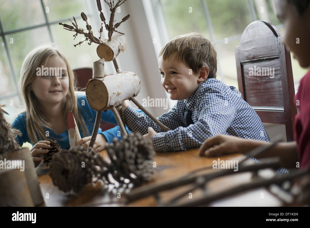Three children sitting at a table in family home A twig reindeer in the centre with branches and twigs to make objects - Stock Image