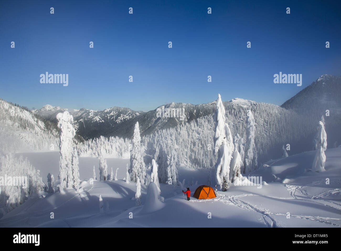Michael Hanson walks through deep powder to his campsite in the snow covered Cascade Mountains overlooking Snow Lake - Stock Image