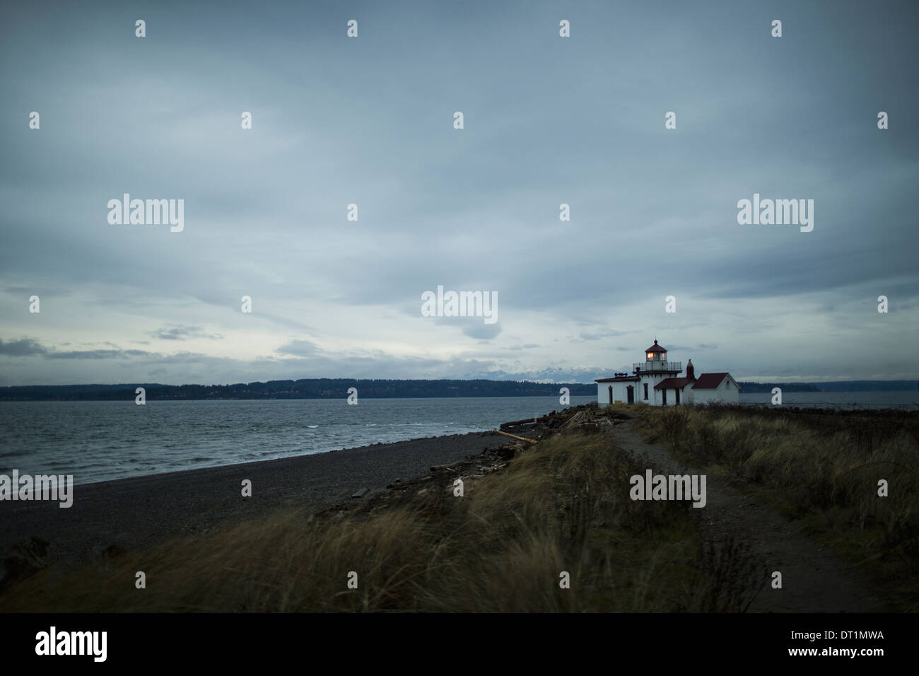 The lighthouse at dusk at Discovery Park in Seattle WA - Stock Image