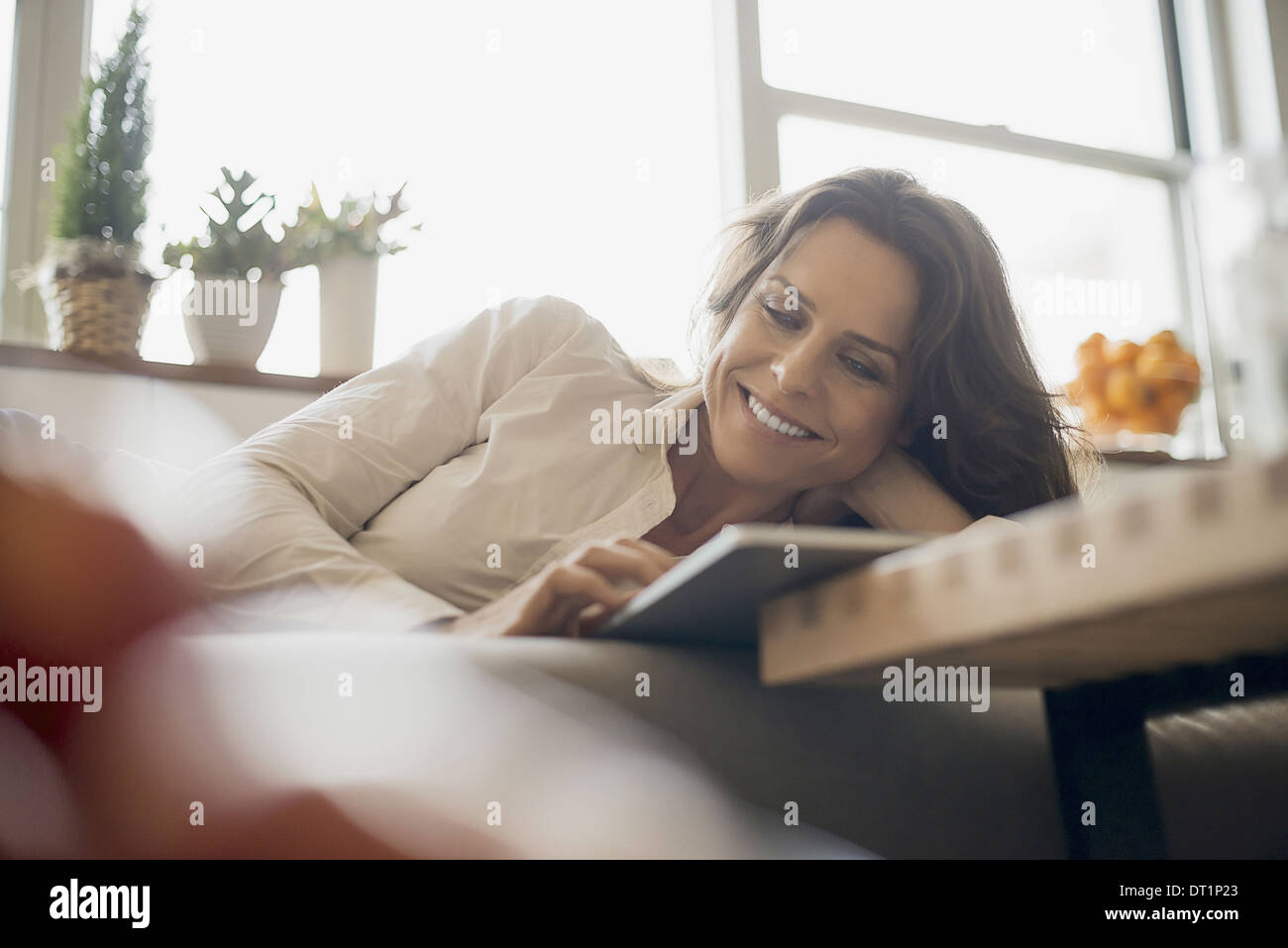 Woman at home using electronic tablet - Stock Image