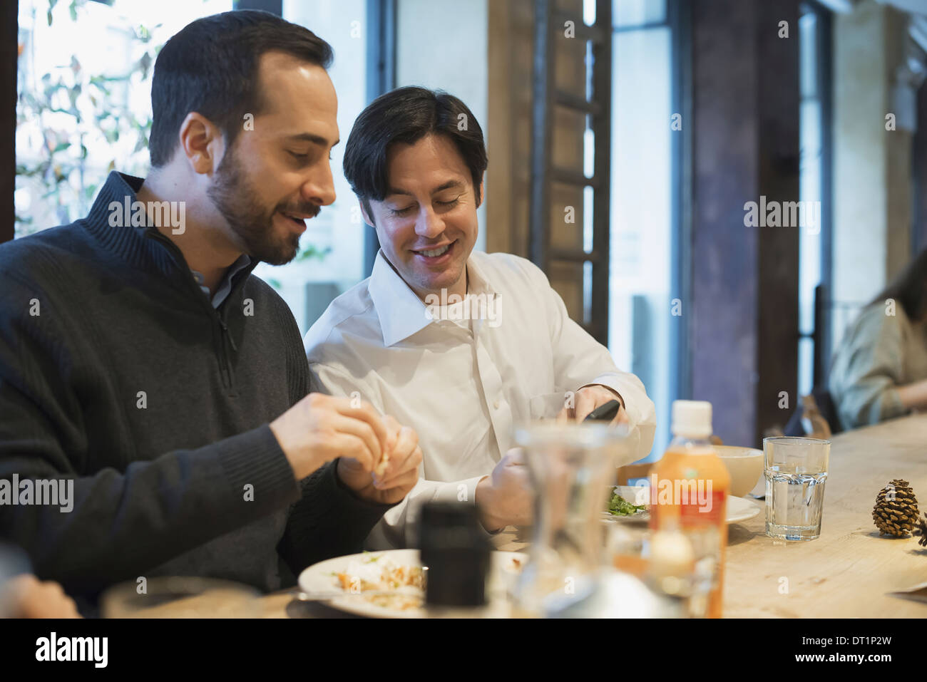 Men sharing text at restaurant table - Stock Image