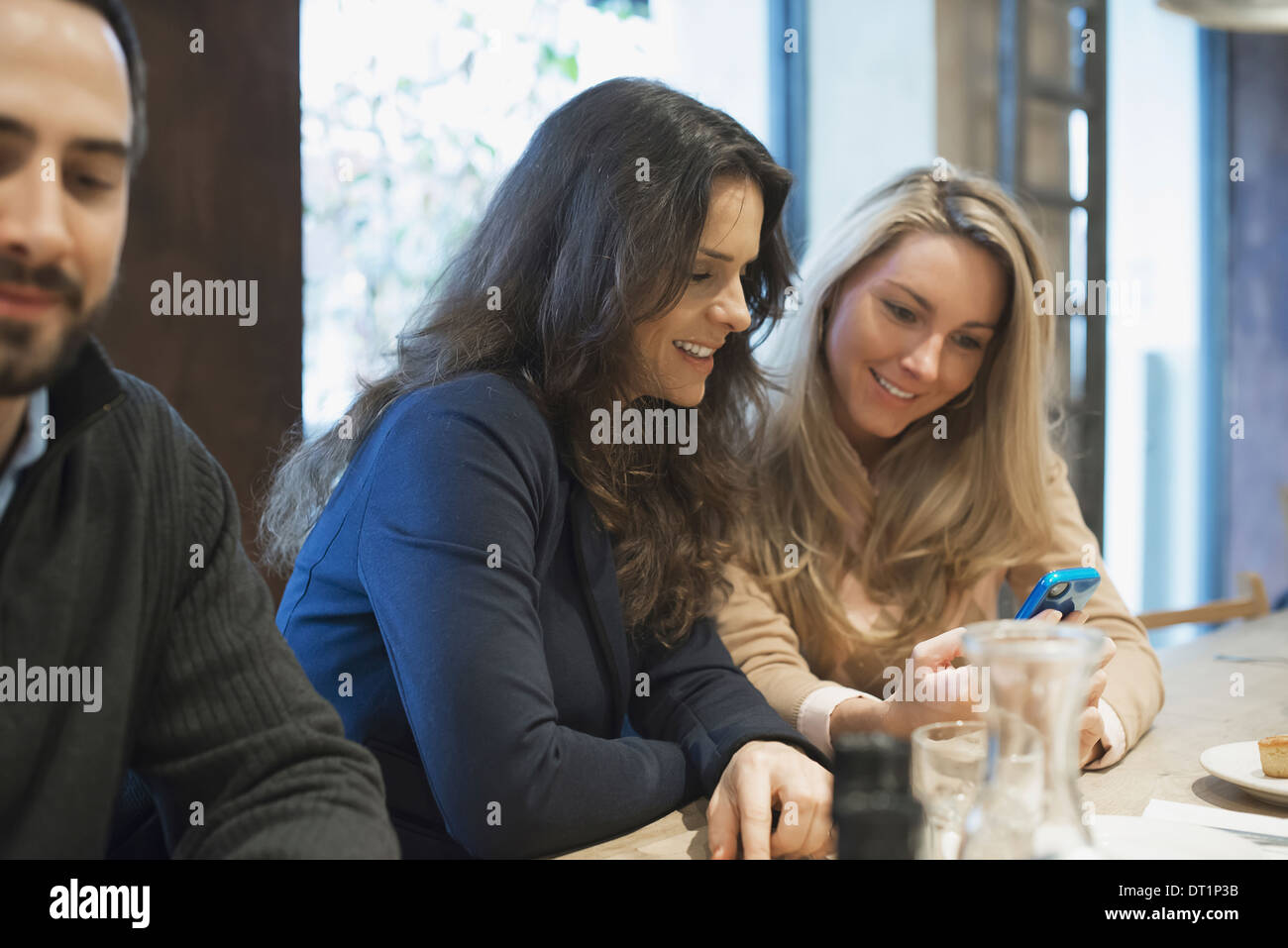 Women sharing text at restaurant table - Stock Image