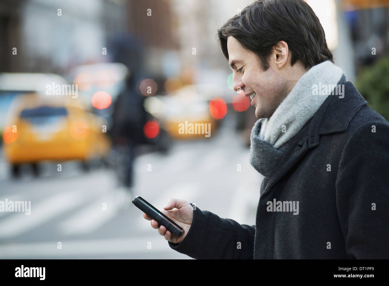 Man on busy street with smartphone - Stock Image