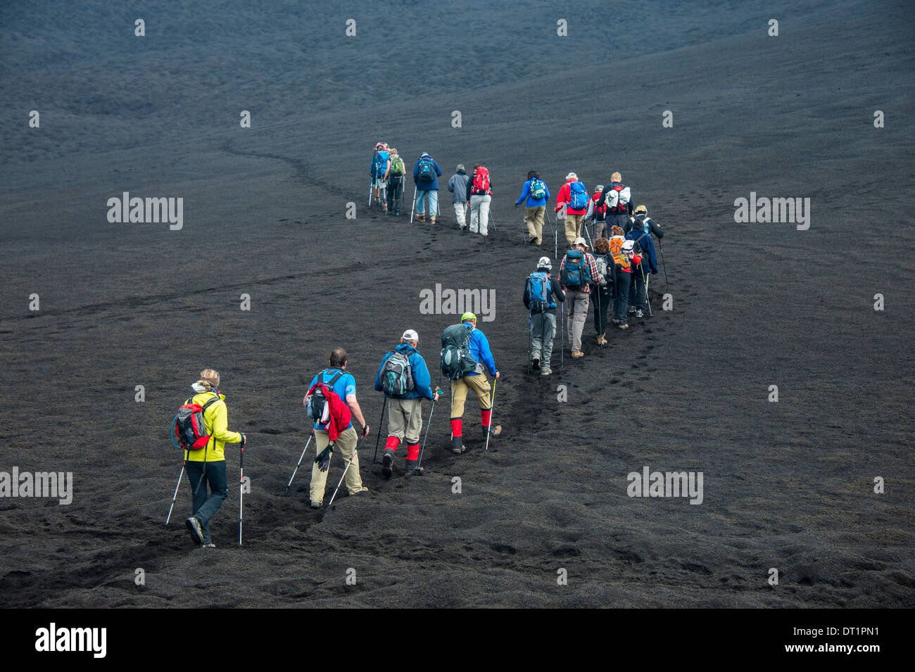 Tourists walking in a line through the lava sands of the Tolbachik volcano, Kamchatka, Russia, Eurasia - Stock Image