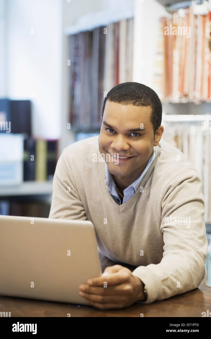 Man working in design shop with laptop - Stock Image