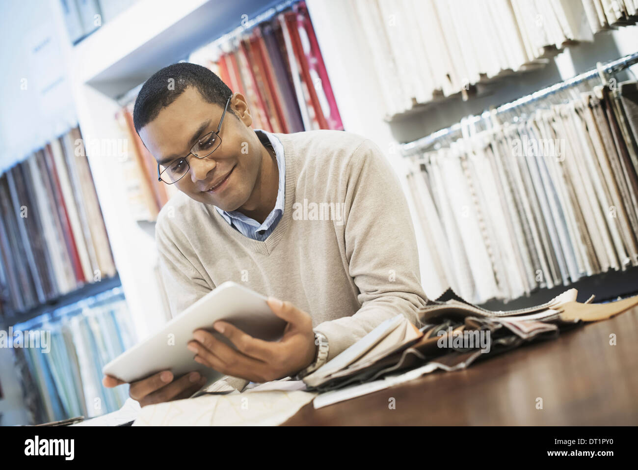 Man working in design shop with tablet - Stock Image