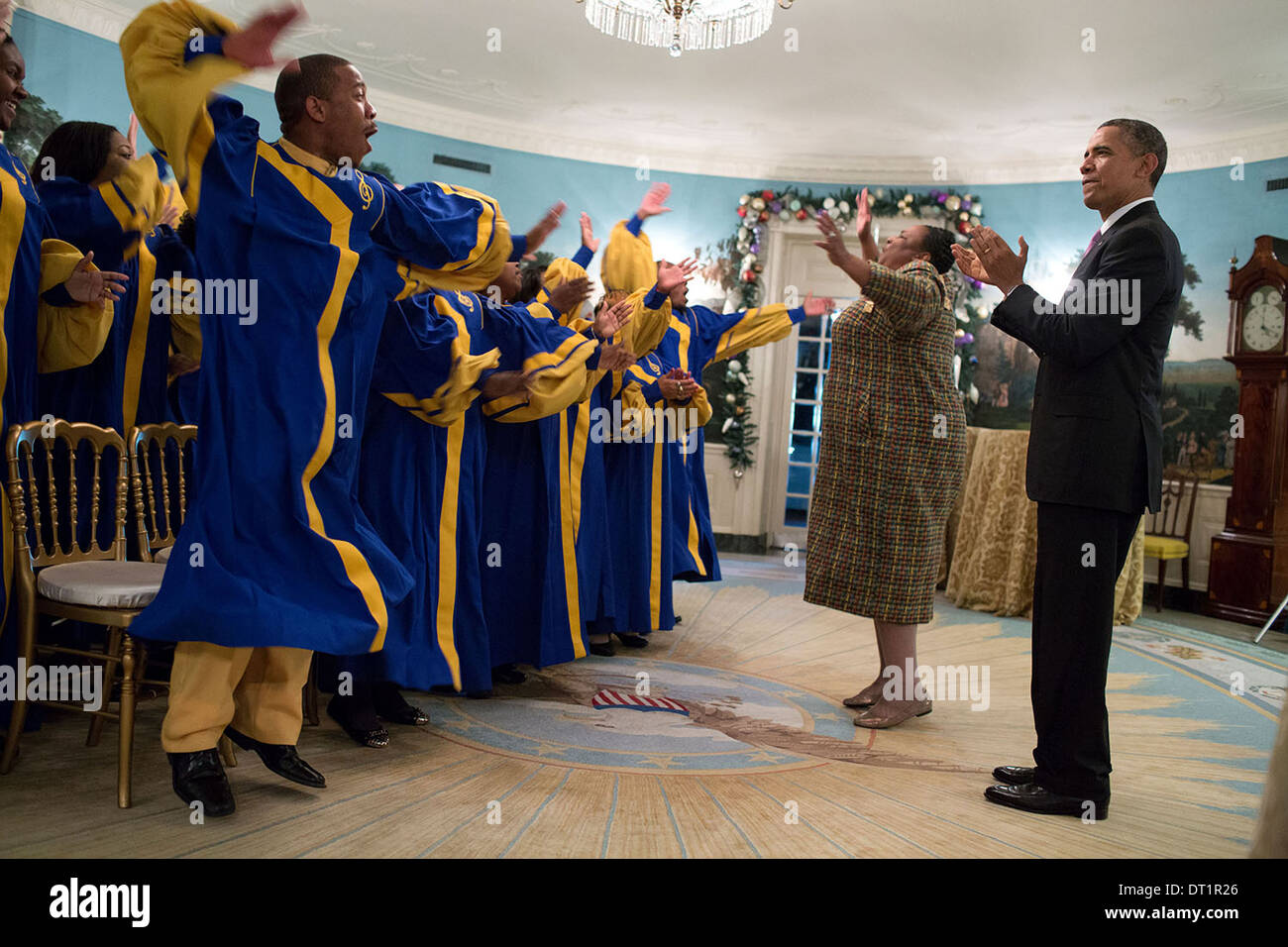 US President Barack Obama listens to the Crenshaw Elite Choir perform in the Diplomatic Reception Room of the White House following a Christmas holiday reception December 11, 2013 in Washington, DC. - Stock Image