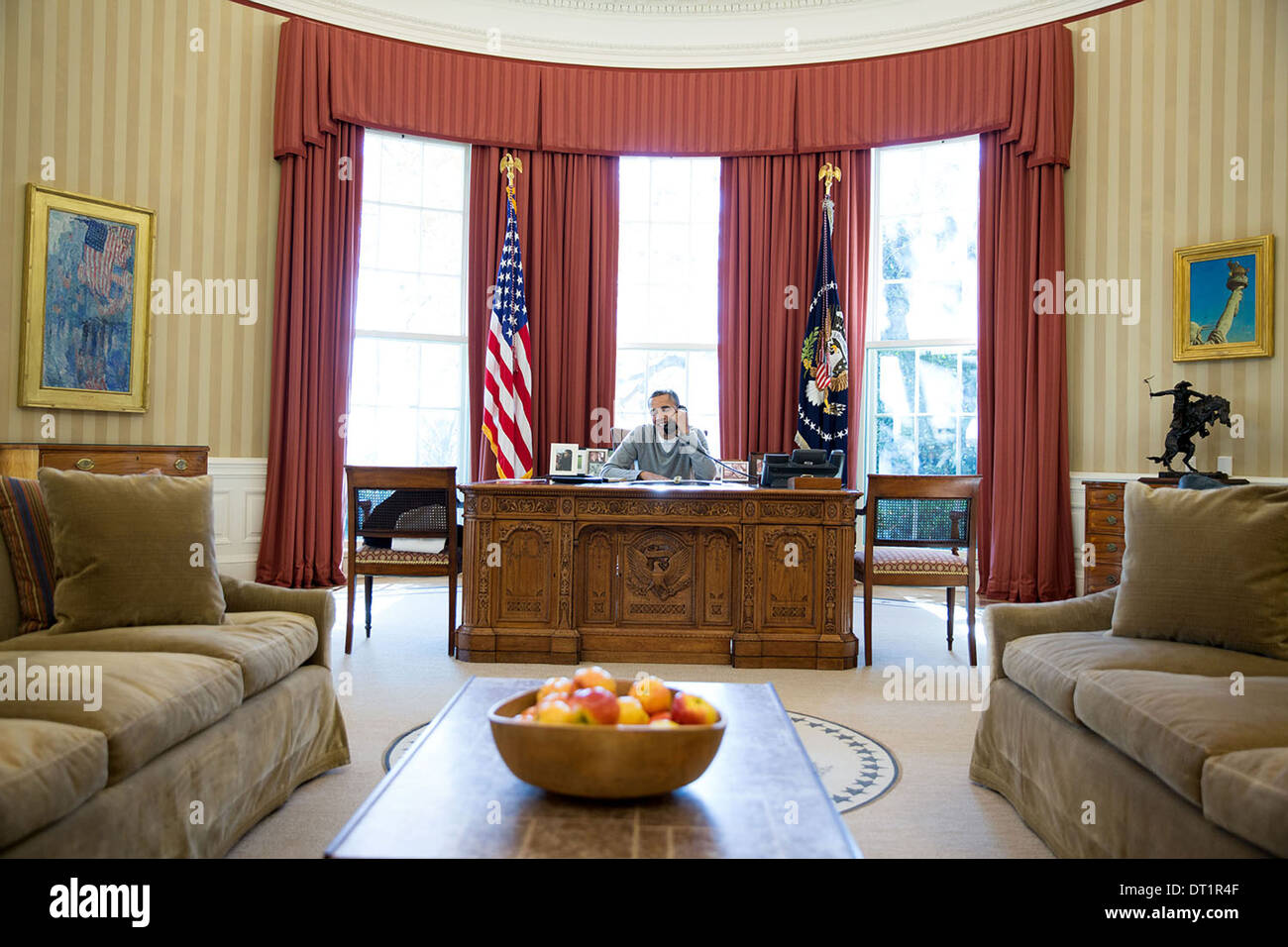 US President Barack Obama makes Thanksgiving Day phone calls to U.S. troops from the Oval Office of the White House November 28, 2013 in Washington, DC. - Stock Image