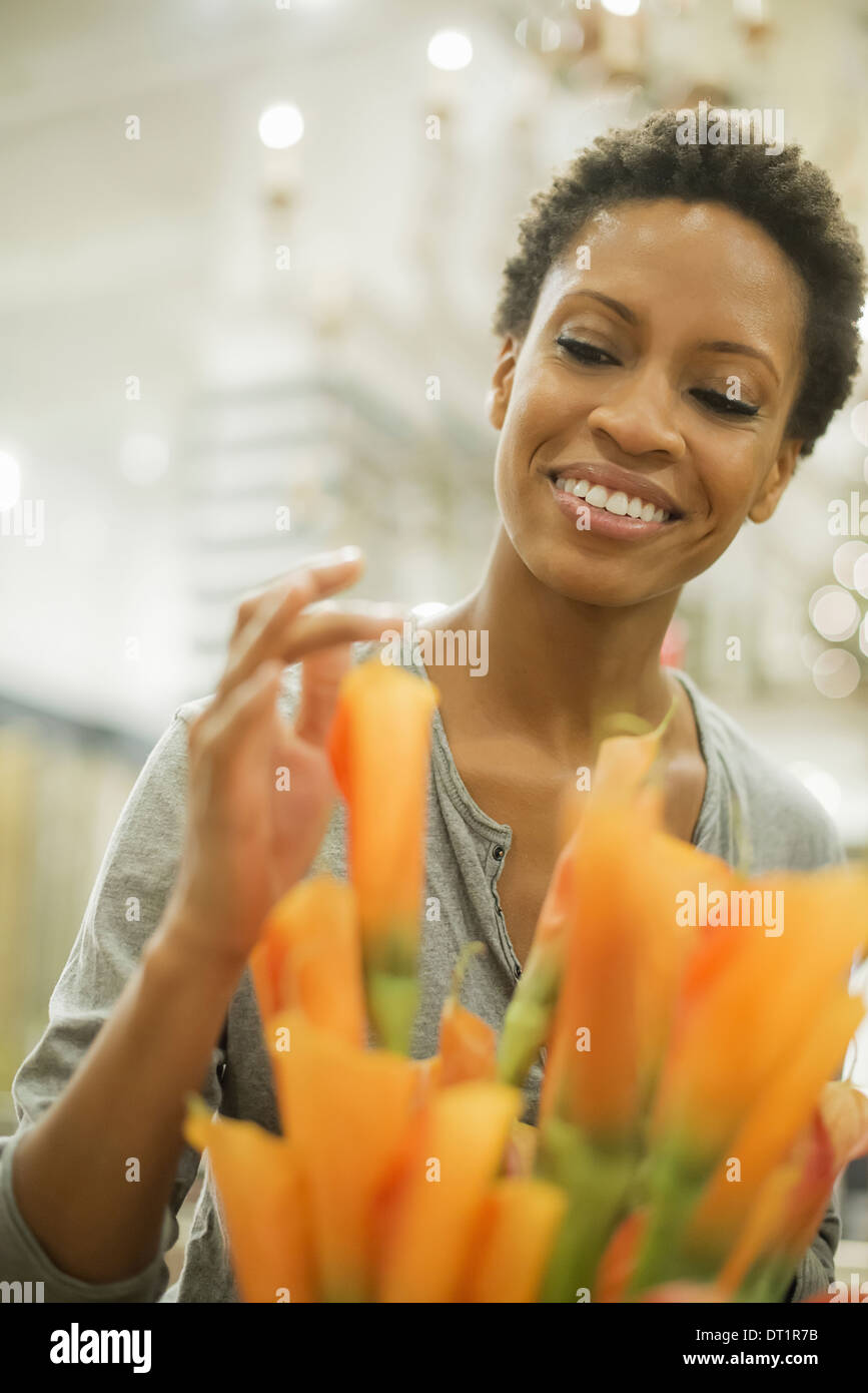 Woman arranging flowers at home - Stock Image