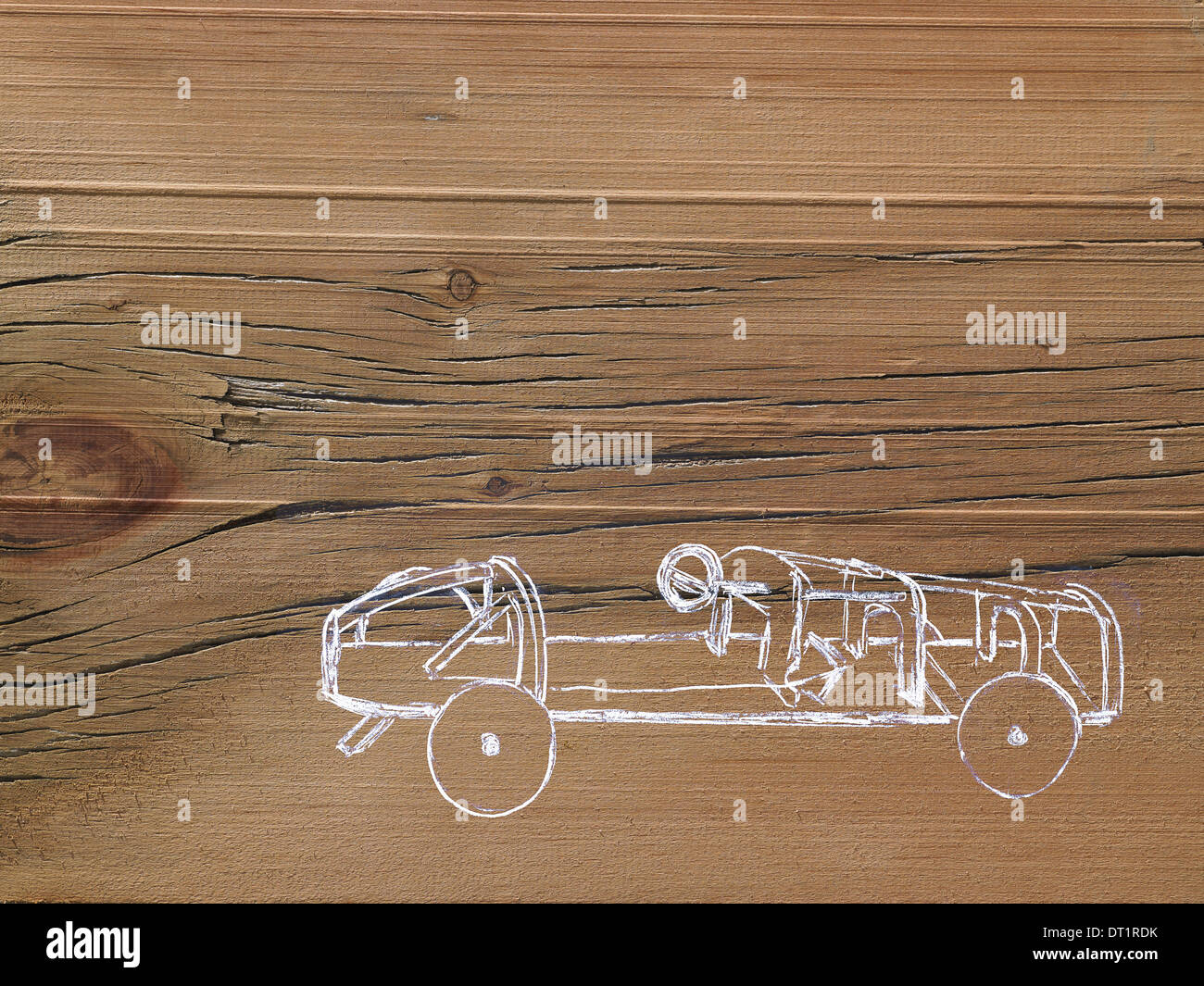 A line drawing image on a natural wood grain background Side profile of a low sporty open top car chassis - Stock Image