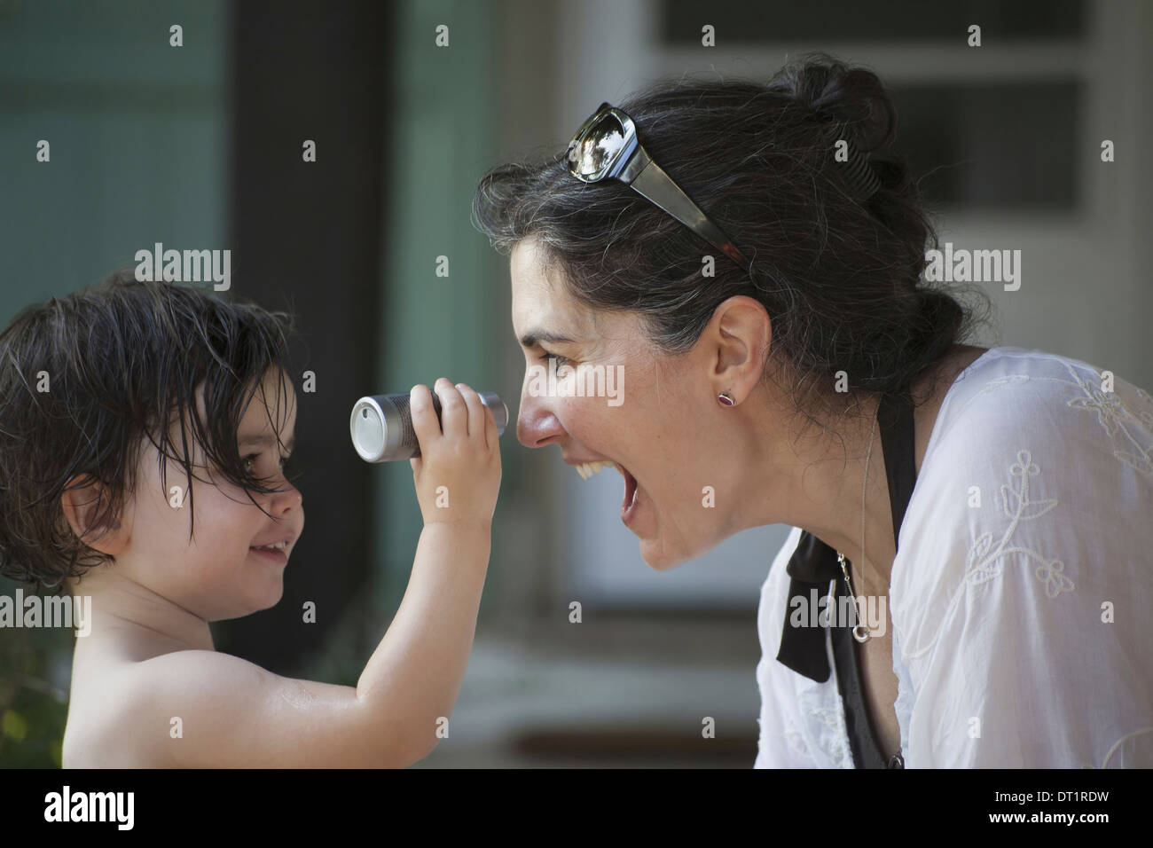 A mother and young daughter face to face playing and laughing - Stock Image