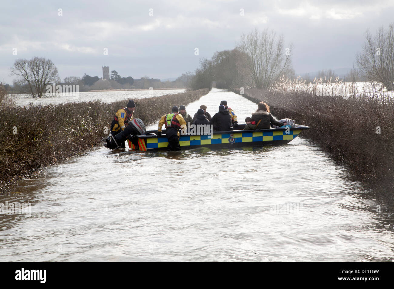 Emergency services humanitarian boat service for cut-off residents of Muchelney, near Langport, Somerset Levels, England - Stock Image