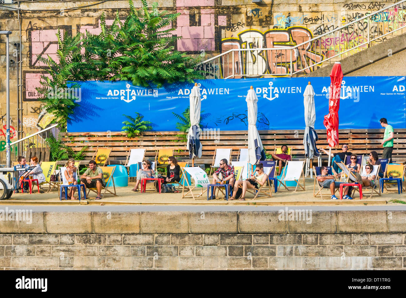 young people relaxing after work at the _adriawien_ beach cafe on the shores of the danube canal, vienna, austria - Stock Image