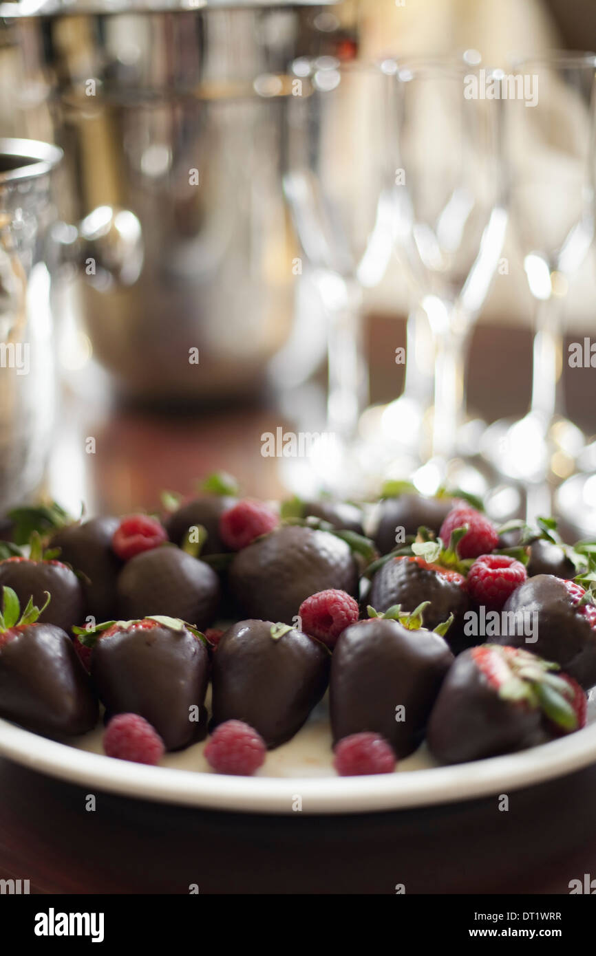 Wedding dessert Plate of hand-dipped organic strawberries fruit in artisanal handmade chocolate with raspberry garnish - Stock Image