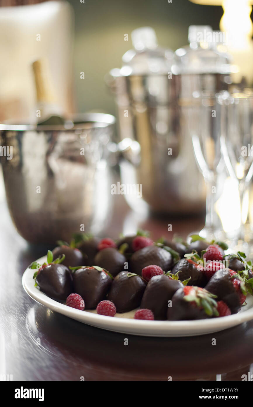 Plate of hand-dipped organic strawberries fruit in artisanal handmade chocolate with raspberry garnish Champagne and glasses - Stock Image